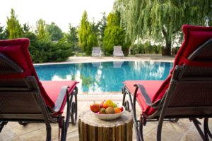 Two red lounge chairs by an outdoor in ground pool.