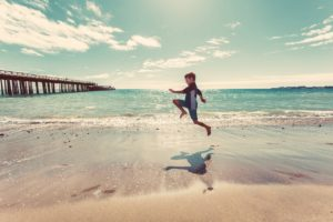 Young boy skipping on the beach.