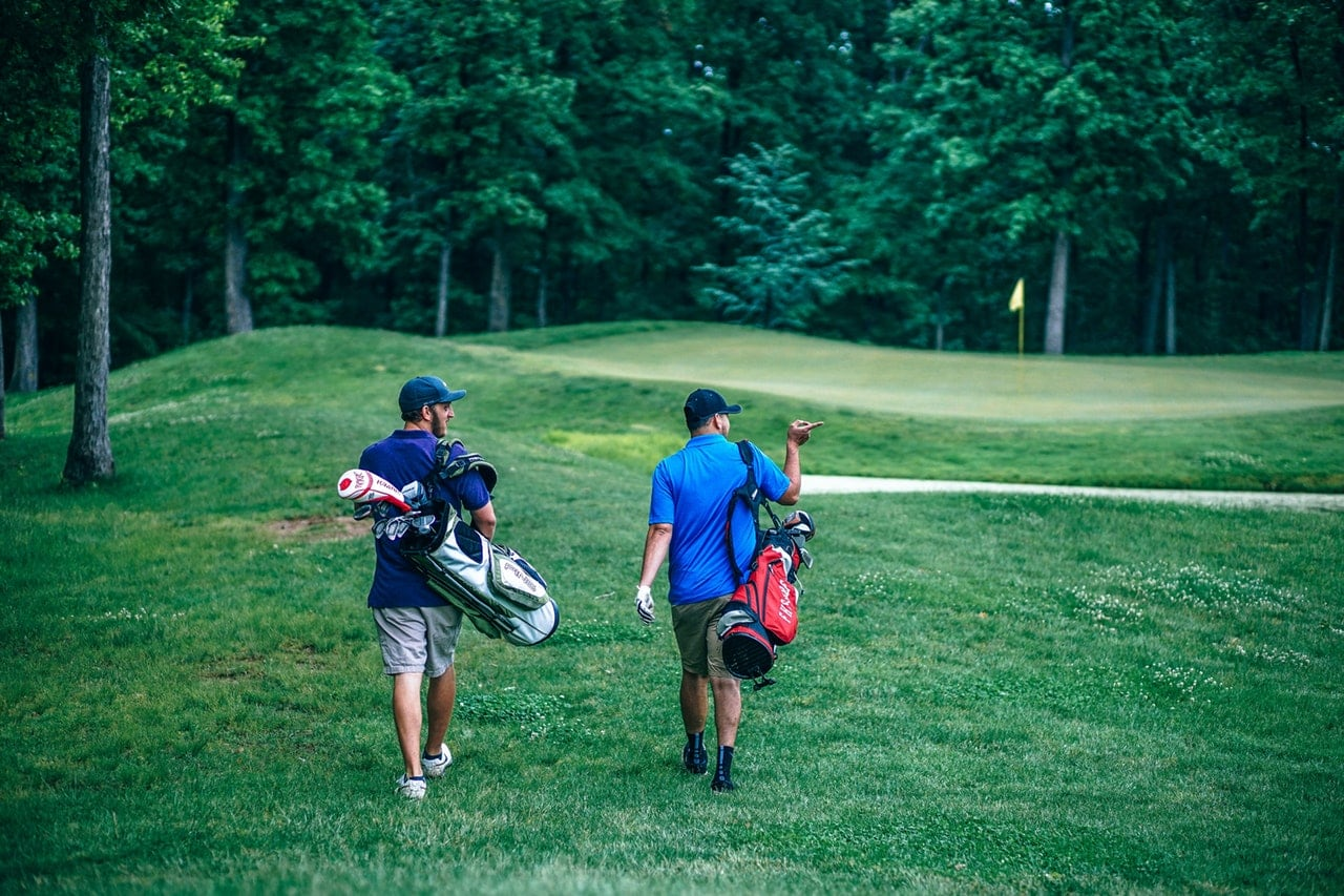 Two men walking across a golf course, carrying their clubs.