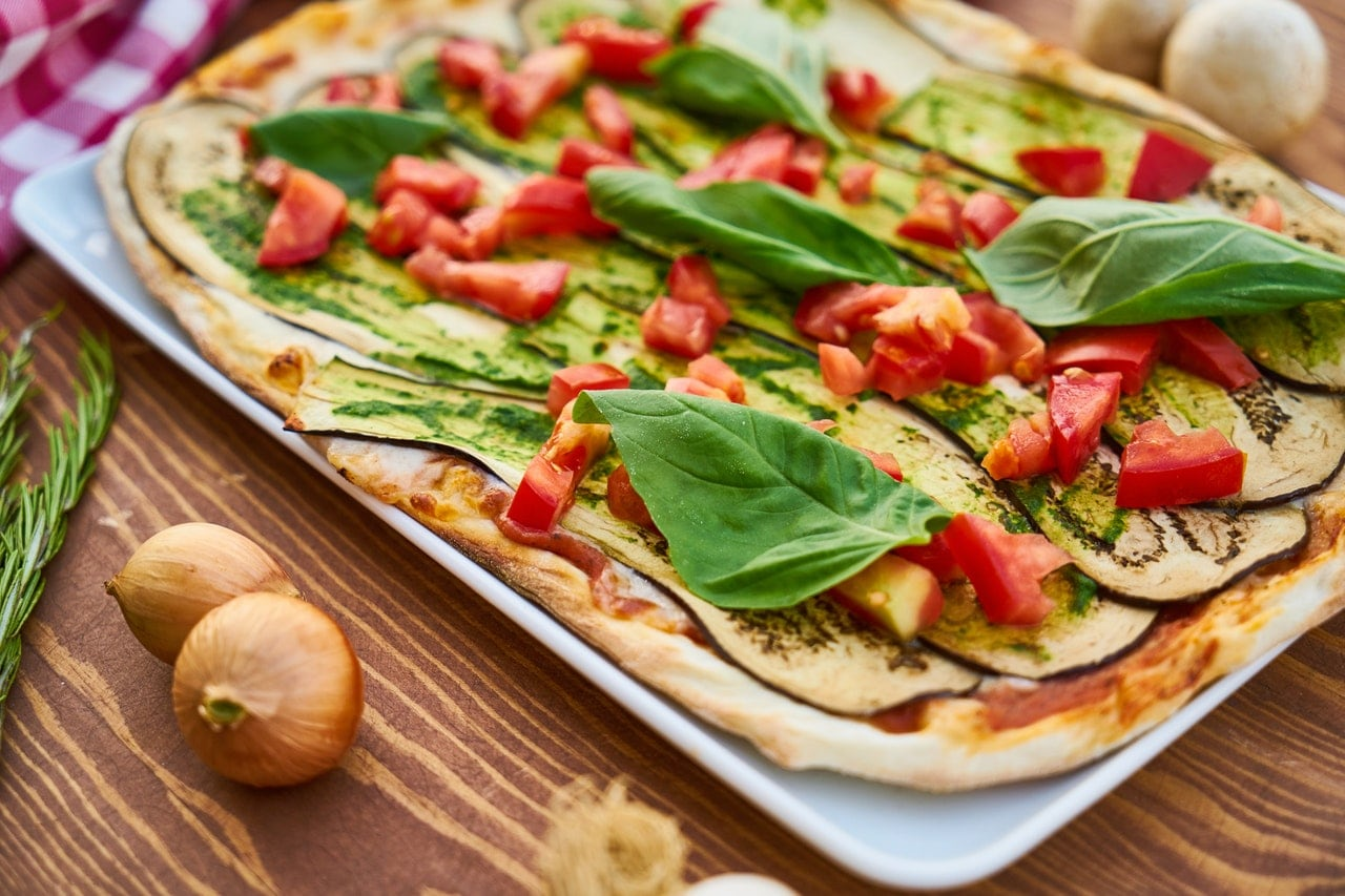 Eggplant parmesan on a flatbread topped with basil.