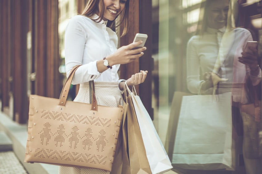 A woman holding large shopping bags and a cell phone as she browses a store.