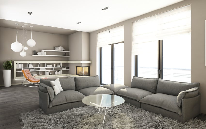 A living room with a sectional sofa, shag rug, and glass coffee table.