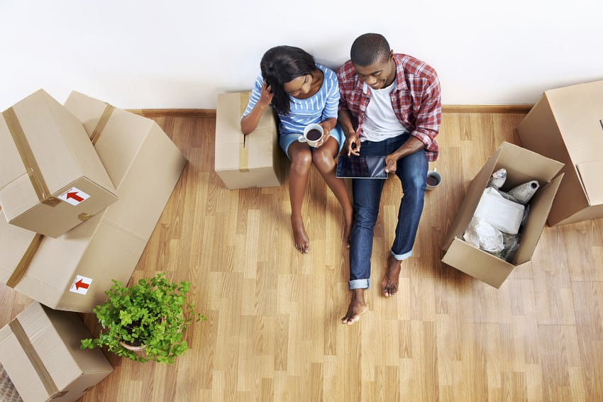 A young couple sitting on the floor next to their moving boxes.