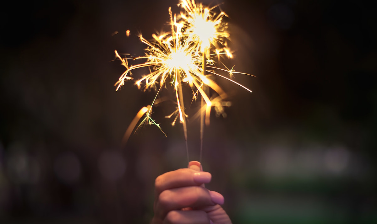 A woman holding a sparkler at night.