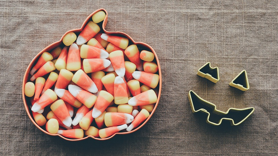 Candy corn in a pumpkin shaped bowl.