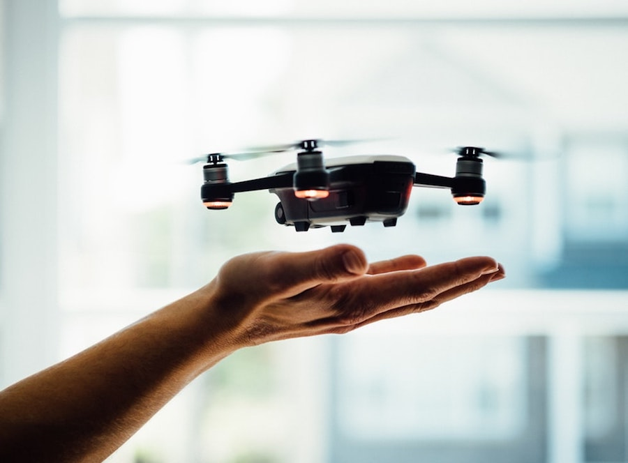 A drone hovering above a person's hands.