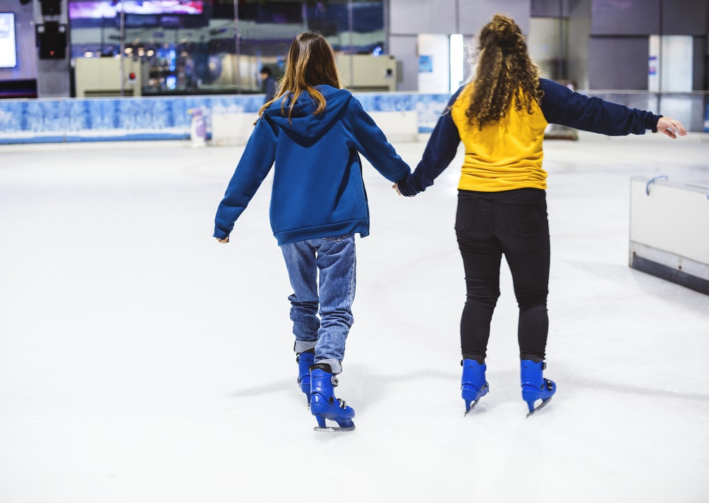 Two girls ice skating at an indoor ink.