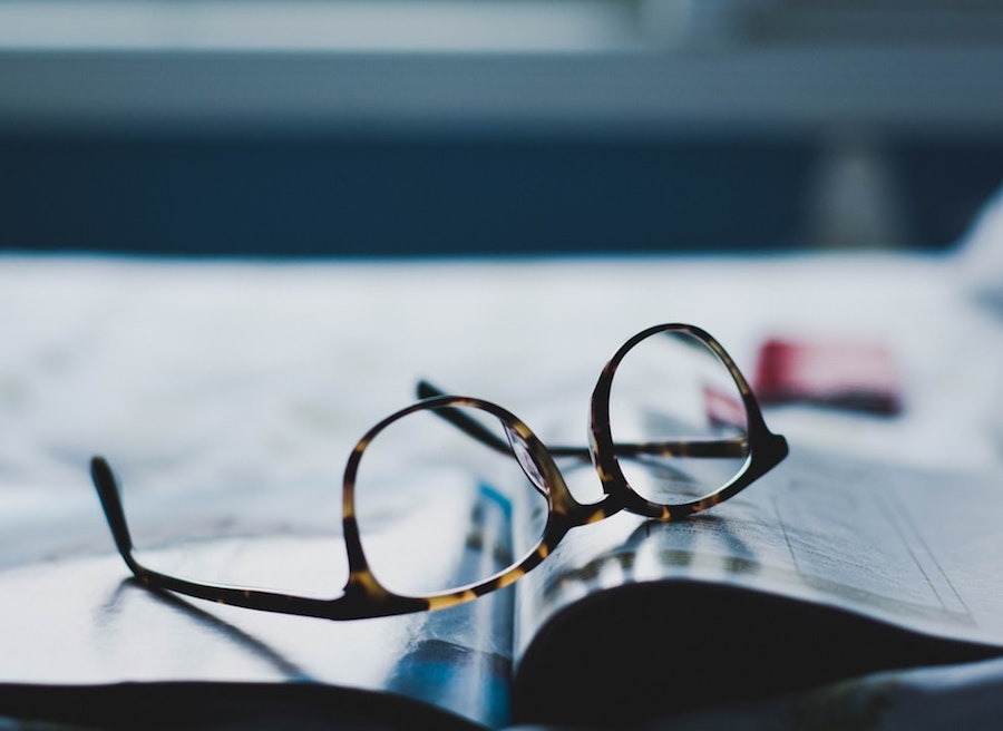 A pair of glasses sitting on a print publication.