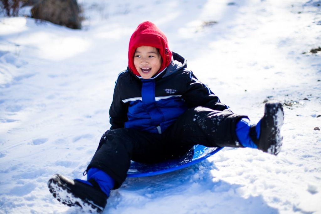 A little kid sledding down a snow hill.